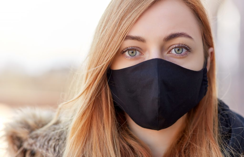 Girl wearing face mask in winter conditions