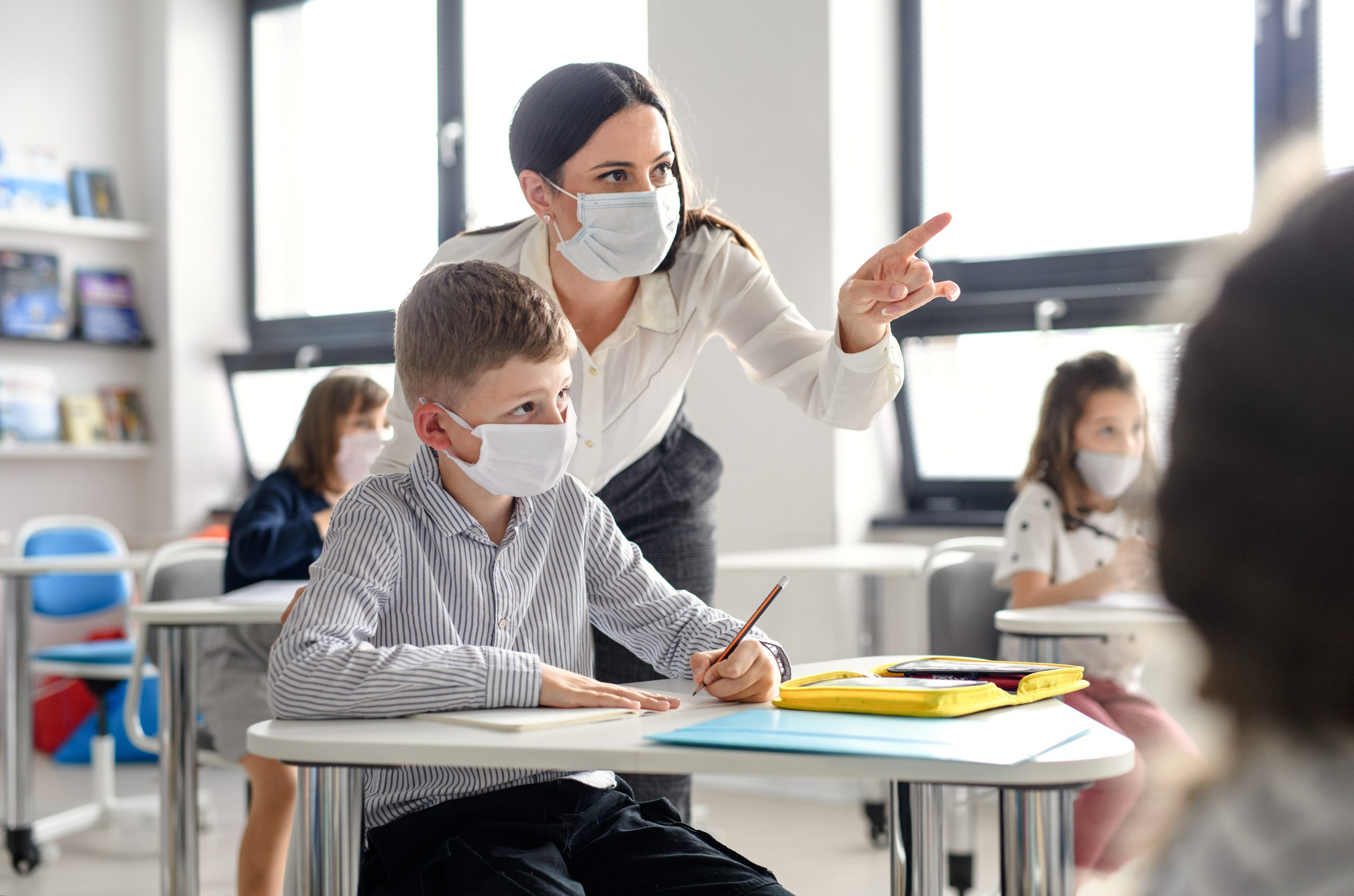 teacher and child wearing masks during lessons